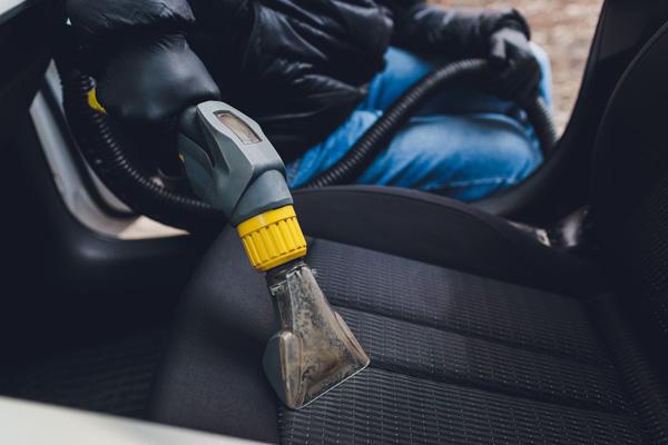 car detailer performing vacuuming interior cleaning