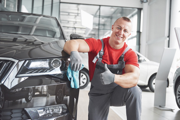 professional car washer smiling detailing service
